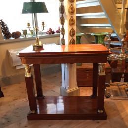 Konsolbord i mahogny med förgyllda detaljer. Tidig empire, c:a 1810-tal. Troligen ritat av Carl Christoffer Gjörwell och utfört av Jonas Frisks verkstad. (Ej signerat).