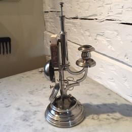 """Förnicklad """"multiljusstake"""" från sekelskiftet 1800/1900 innehållande ljusstake, cigarrsnoppare, cigarrhållare, betjäntsklocka, fickursställ, tändstickshållare."""